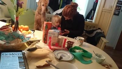 Hund, barn och fru vid frukostbordet